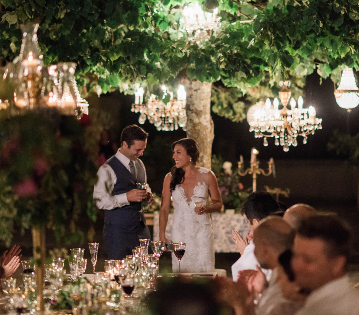 wedding dinner with chandeliers in the trees in a Tuscan vineyard