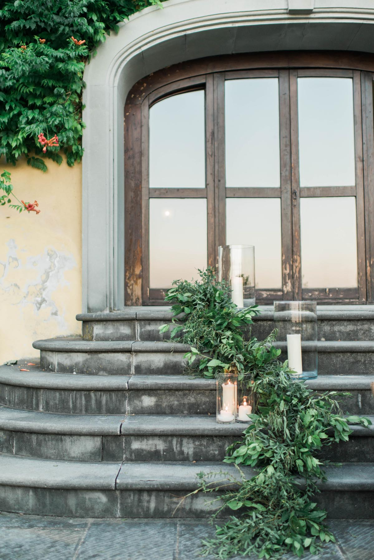 wedding green garland with candles on steps at a Tuscan vineyard