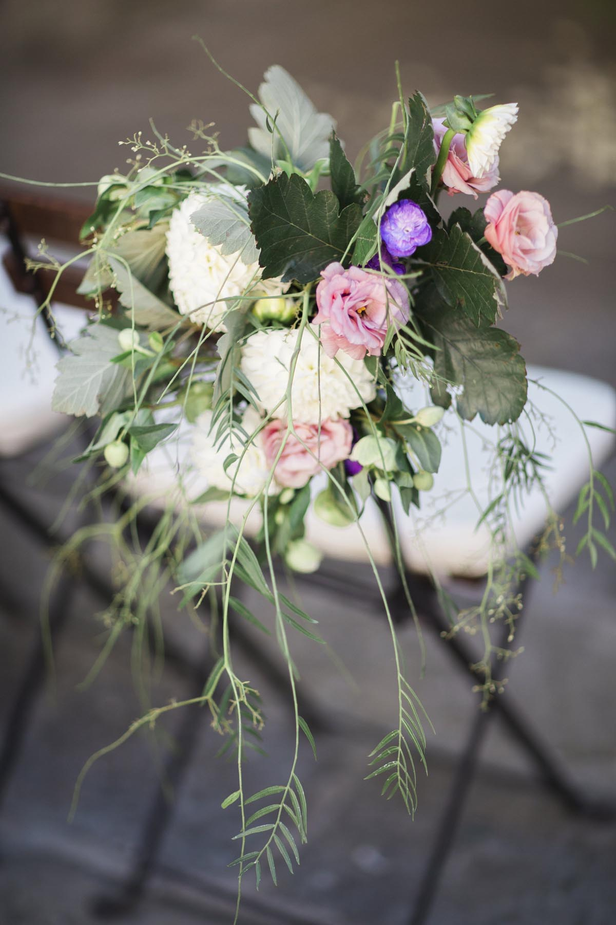 wedding-ceremony-chairs-with-flowers-on-end-of-chairs-with-peonies-and-roses-and-greens
