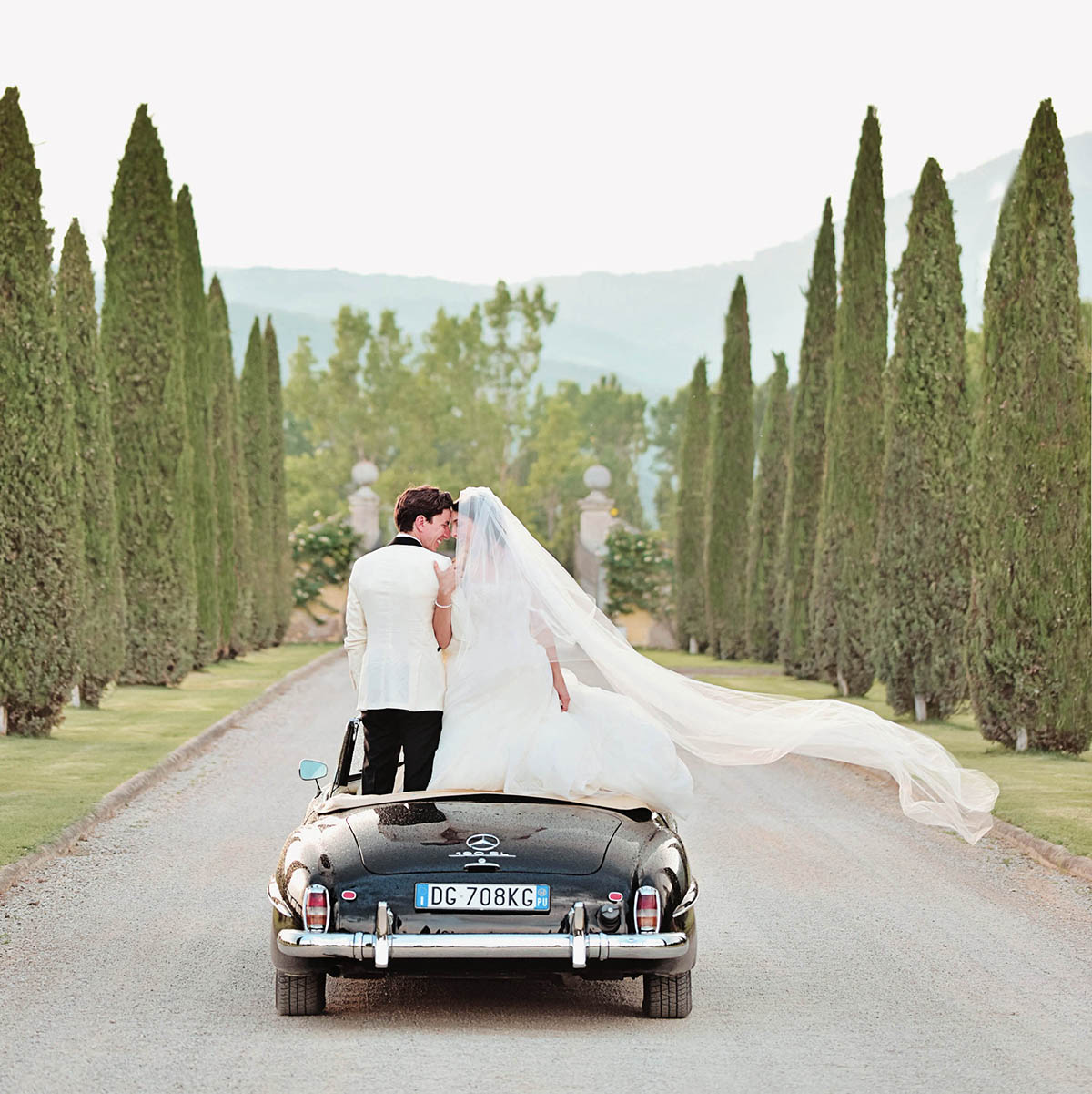 best-luxury-wedding-planner-Tuscany-Italy-with-convertible-vintage-car-and-cypress-trees